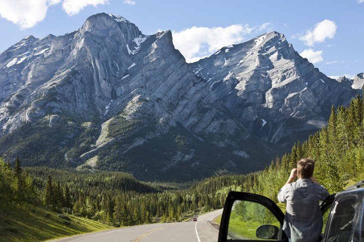 man standing by car looking at mountain on Icefields Parkway