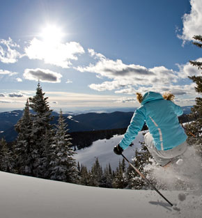ski sun peaks - woman jumping through powder with lake and mountain view
