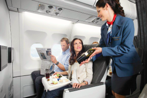 Passengers relax in leather seats in Air Transat CLub Class as flight attendant offers bottle of wine