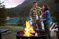 Couple cooking on a fire at Lake Louise