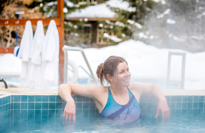 woman relaxing in spa surrounded by snow